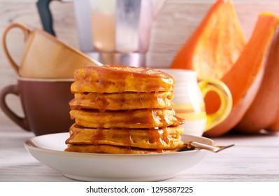 Pumpkin pancakes with caramel sauce on plate