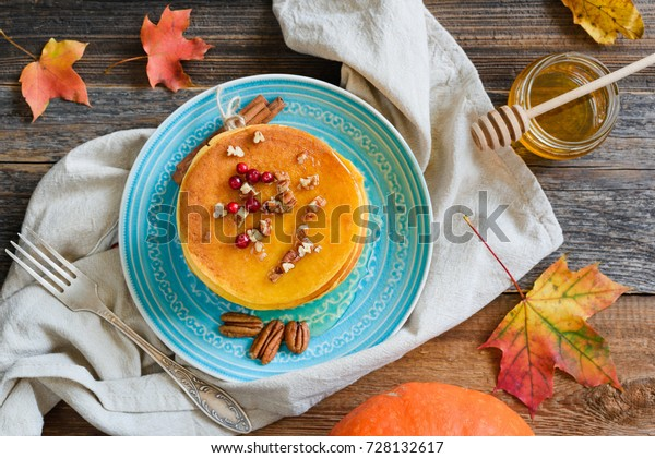 Pumpkin pancakes with honey, pecan nuts and berries on a plate. Table top view. Homemade pumpkin pancakes autumn food