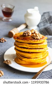 Pumpkin pancakes with maple syrup or honey and walnuts on a white plate. Grey concrete Copy space. Healthy breakfast. Autumn food