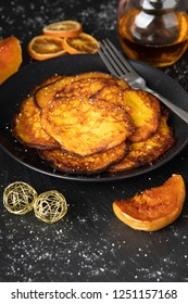Pumpkin pancakes on a black plate