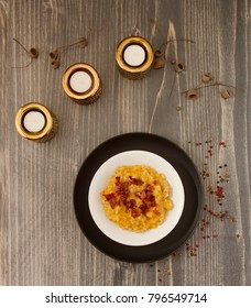 Pumpkin and pearl barley porridge with bacon on wooden background