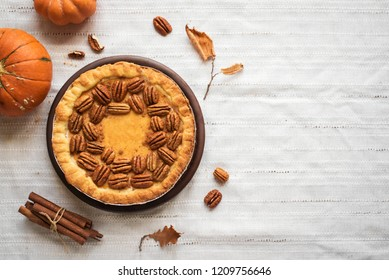 Pumpkin and Pecan Pie with cinnamon on white linen background, top view, copy space. Homemade autumn pastry for Thanksgiving.