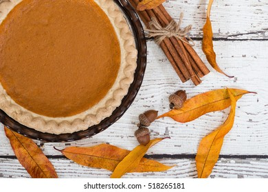 Pumpkin pie with autumn decorations on vintage wooden table. Top view.