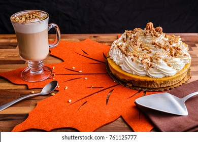 Pumpkin pie cheesecake and a cup of latte coffee.  Setting on an orange leaf placemate with spoon and pie knife.  Cheesecake is covered with whipped cream and pecans, then drizzled with caramel syrup.