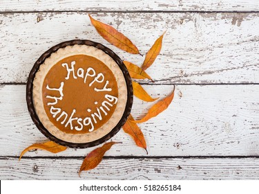 Pumpkin pie with Happy Thanksgiving text. Displayed with golden autumn leaves on vintage, wooden table. Top view.