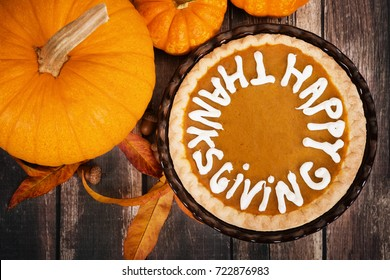 Pumpkin pie with Happy Thanksgiving text. Displayed with pumpkins, golden autumn leaves, and acorns on vintage, wooden table. Top view.