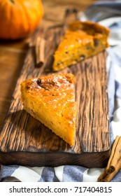 Pumpkin pie on chopping board. Rustic background. Selective focus.