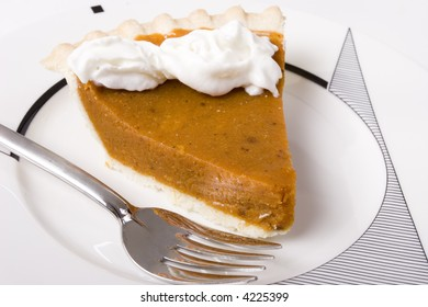 Pumpkin pie on fancy plate and a fork