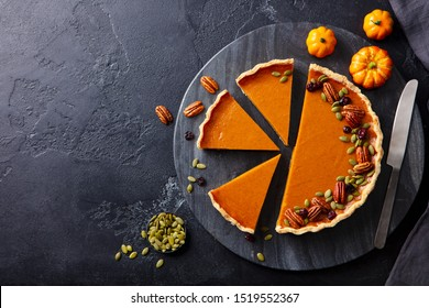Pumpkin pie on marble cutting board. Dark background. Copy space. Top view.