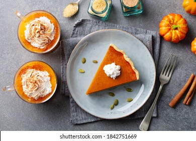 Pumpkin pie on a plate, pumpkin latte with whipped cream. Grey background. Top view.
