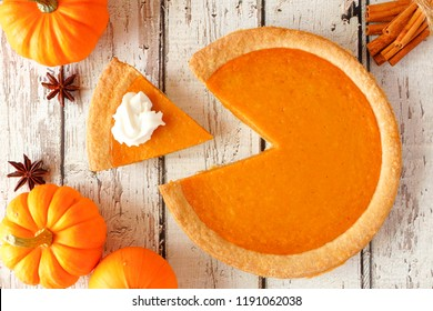 Pumpkin pie with slice removed.  Top view table scene on a rustic white wood background.