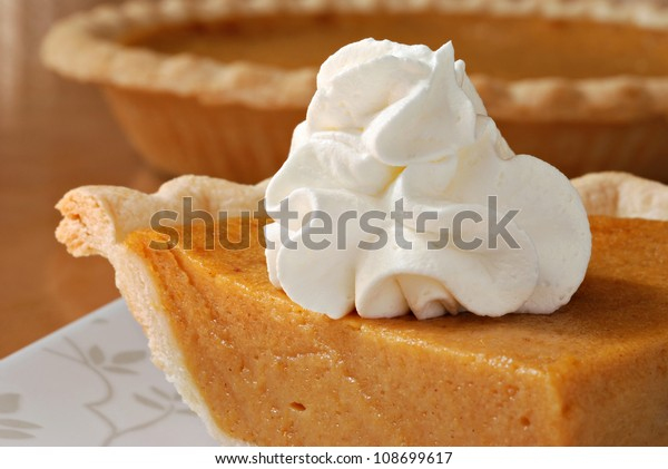 Pumpkin pie with swirls of whipped cream on decorative plate.  Whole pie in soft focus in background.  Macro with shallow dof.
