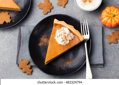 Pumpkin pie, tart made for Thanksgiving day with whipped cream on a black plate. Grey stone background Top view