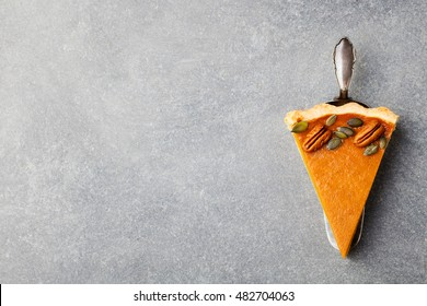 Pumpkin pie, tart made for Thanksgiving day. Grey stone background. Top view Copy space