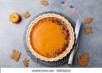 Pumpkin pie, tart made for Thanksgiving day with American flag Grey stone background. Top view. Copy space