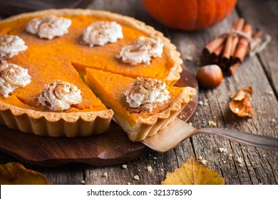 pumpkin pie with whipped cream and cinnamon on rustic background, top view