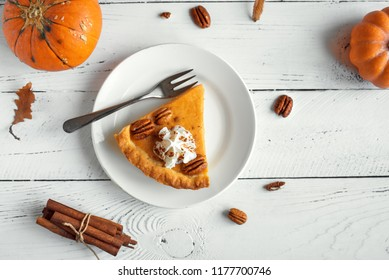 Pumpkin Pie with whipped cream, pecan nut and cinnamon on white wooden background, top view, copy space. Homemade autumn pastry for Thanksgiving - piece of pumpkin pie.