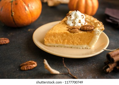 Pumpkin Pie with whipped cream, pecan nut and cinnamon on rustic background, top view, copy space. Homemade autumn pastry for Thanksgiving - piece of pumpkin pie.