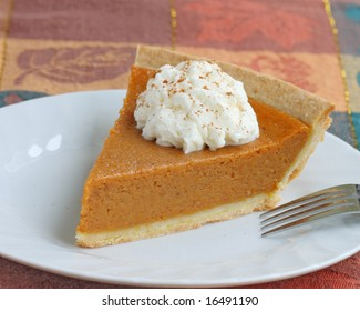 pumpkin pie with whipped cream served on white plate