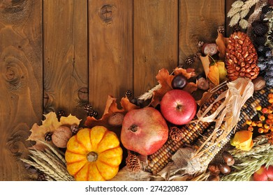 pumpkin, pomegranate, apple, nuts, berries and grain on old weathered wooden floor