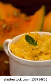 Pumpkin porridge and pumpkins on wooden table