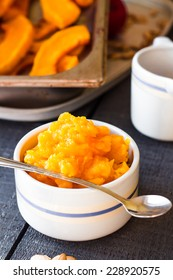 pumpkin puree in a ceramic bowl with spoon, healthy dessert on a wooden board
