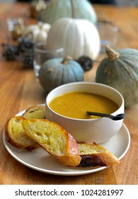 Pumpkin puree cream with french baguette on wooden table with pumpkin background.