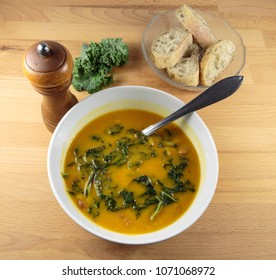 Pumpkin, red lentils and kale delicious soup in a white bowl