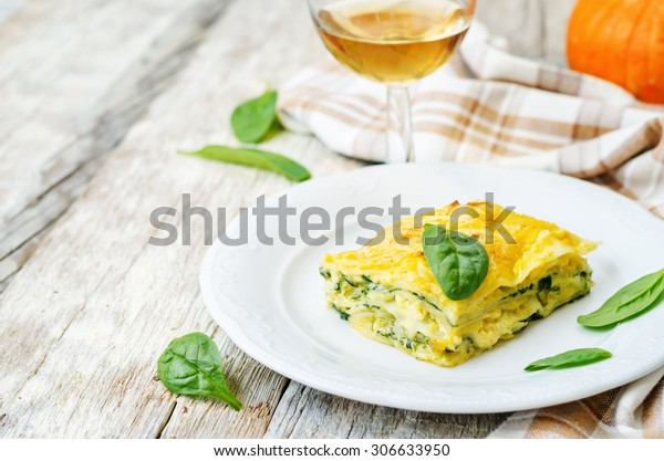 pumpkin ricotta spinach lasagna on a white wood background. the toning. selective focus