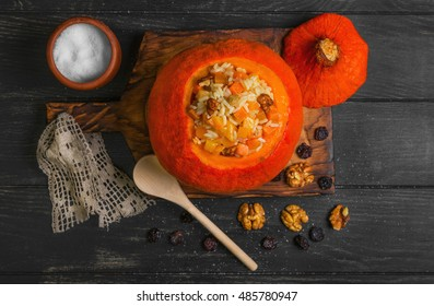 Pumpkin risotto with raisins. Rice porridge with sweet pumpkin, raisins, nuts. Baked pumpkin Halloween for rice. Sugar, dark wooden background. Top view
