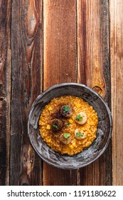Pumpkin risotto with scallops in a bowl, wooden background, copy space.