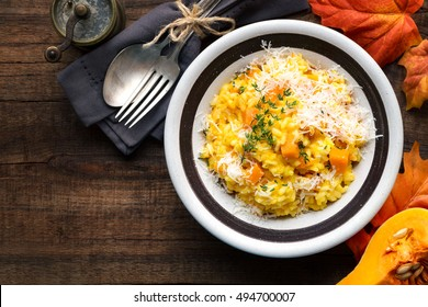 Pumpkin risotto with thyme and parmesan cheese against dark wooden background. Overhead view with copyspace for your text