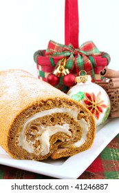 Pumpkin roll on a white plate and surrounded by Christmas decorations.  Room for your text.