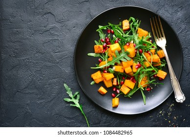 Pumpkin salad with pomegranate seed and arugula on a black plate over dark slate, stone or concrete background.Top view with copy space.