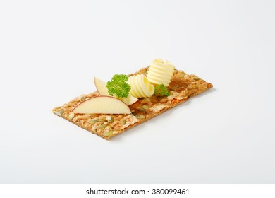 pumpkin seed cracker with butter curls and apple slices on white background