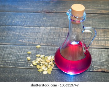 pumpkin seed oil in a glass decanter on a wooden table