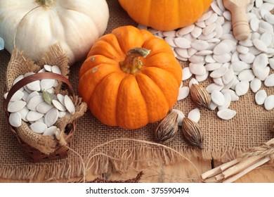 Pumpkin with pumpkin seeds on wood background