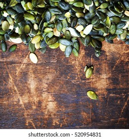 Pumpkin seeds over wood background with copy space
