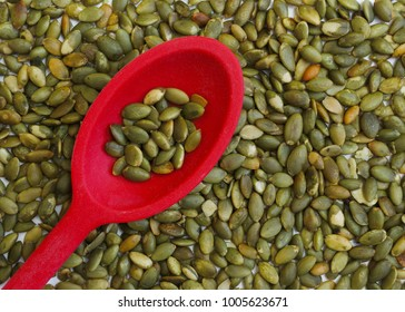 Pumpkin seeds in a red spoon.
