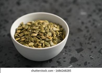pumpkin seeds in white bowl on terrazzo countertop