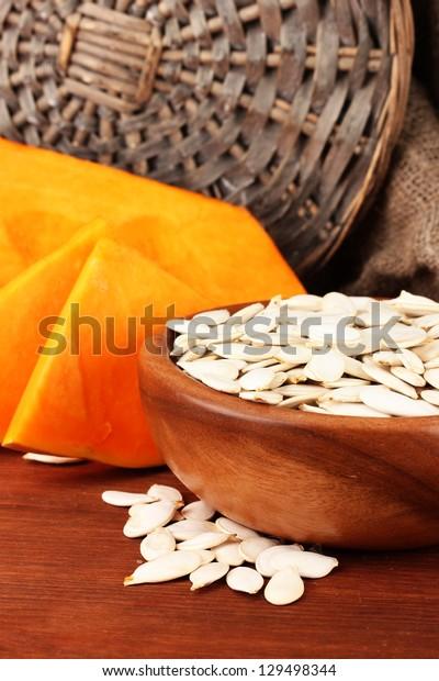 Pumpkin seeds in wooden bowl, on sackcloth background