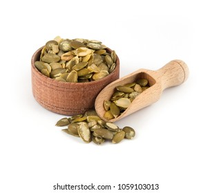 Pumpkin seeds in a wooden bowl with a scoop on a white background.