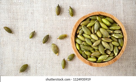 Pumpkin seeds in wooden bowl, top view