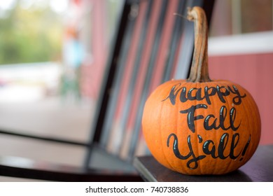 "Pumpkin sitting on table with red building in background. ""Happy Fall Y'all!"" painted on the side."