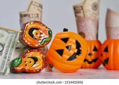 Pumpkin smile face bucket with Dollar, Thai Baht and Japan money on table