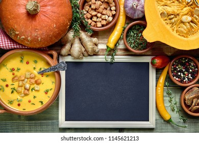 Pumpkin soup background with blank blackboard next to a bowl of soup with a spoon and healthy soup ingredients. Space for your text.