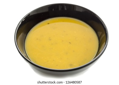 Pumpkin soup in black bowl isolated over a white background.