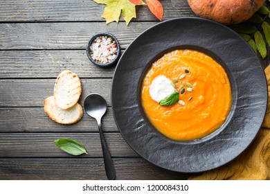 Pumpkin soup in a black plate on dark wooden background. Autumn decorations. Top view
