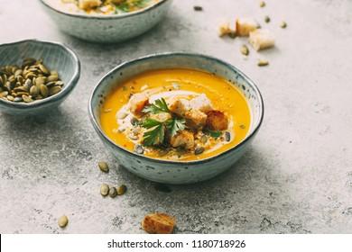 Kürbissuppe in einer Schüssel mit Kürbiskernen und Croutons. Herbstessen.