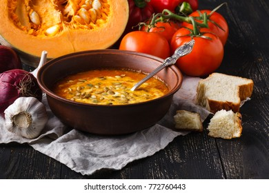 Pumpkin soup in bowl on rustic table with bread